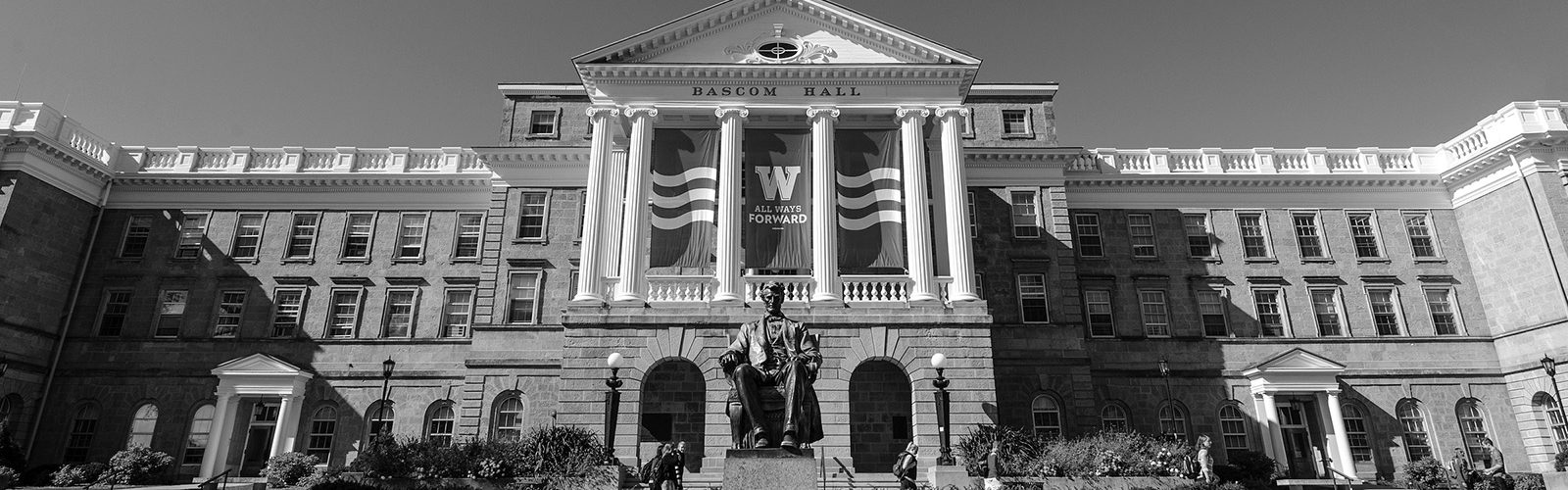 "Red and white banners featuring the iconic W and the phrase ""All Ways Forward"" adorn the exterior of Bascom Hall on a fall day."