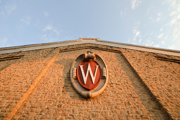 The sun sets on an ornate W crest icon and architectural detail on the side of the Field House at the University of Wisconsin-Madison on Aug. 15, 2013. (Photo by Jeff Miller/UW-Madison)